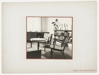 Interior view of a furnished apartment, showing two chairs, a small round table, bookshelves behind. A window at left above a radiator.