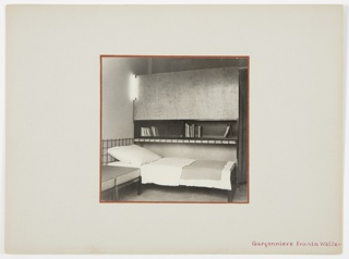 Interior view of the bedroom area of an apartment, with small bed and bookshelf.