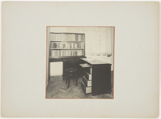 Desk with drawers open, bookshelf behind, curtained window at right.
