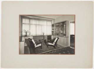 Interior view of living room area of apartment, with two chairs, bookshelf, and carpets.