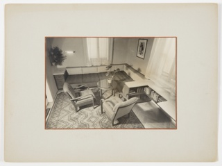 Interior view of corner living room area of apartment, with L-shaped sofa, two chairs, bookshelves, and small around table.