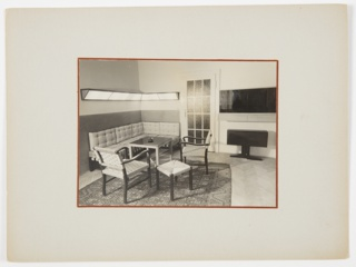 Interior view of a corner living room area in an apartment, with L-shaped sofa, lighting feature above, two chairs, and two small tables on a carpet.