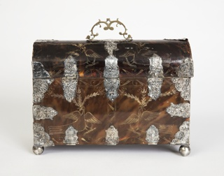 Oblong casket with arched lid hinged at back; engraved decoration featuring birds amidst floral and foliate borders; silver mounts consisting of center lock in form of double eagle, corner and angle plates, loop handle at top of lid, and four ball feet.