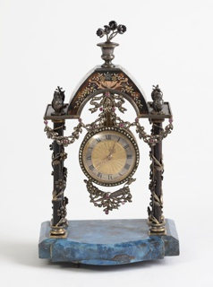 Architectural structure holding circular clock, its border encrusted with diamonds, ribbon motifs surrounding the top and bottom; clock hung from tortoiseshell arch with gold floral vines creeping up the two columns and three gold ornaments positioned on top of each column and arch, all on vase of thick lapis.