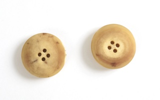 Two circular tan beige to tan buttons; each with four holes.