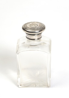 Larger glass bottle with silver top, part of set.