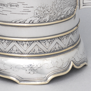 Cylindrical form with applied gold edges and chased with elaborate Chinese landscapes, deep spout, and shaped handle opposite.