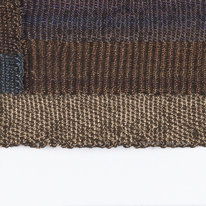Composition of irregular squares and rectangles in shades of brown and blue. The fiber is not dyed. The color changes are the result of changes in the molecular structure of the steel through a process of sequential heating and cooling.