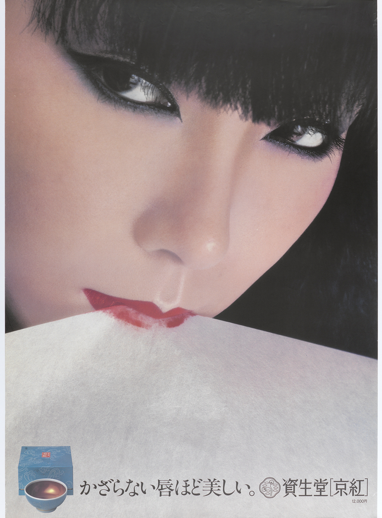 "Face of woman in red lipstick with piece of white paper in her mouth in top half of poster.  Japanese text across bottom, rough translation is close to: ""The less a lip is decorated the more beautiful it is."""