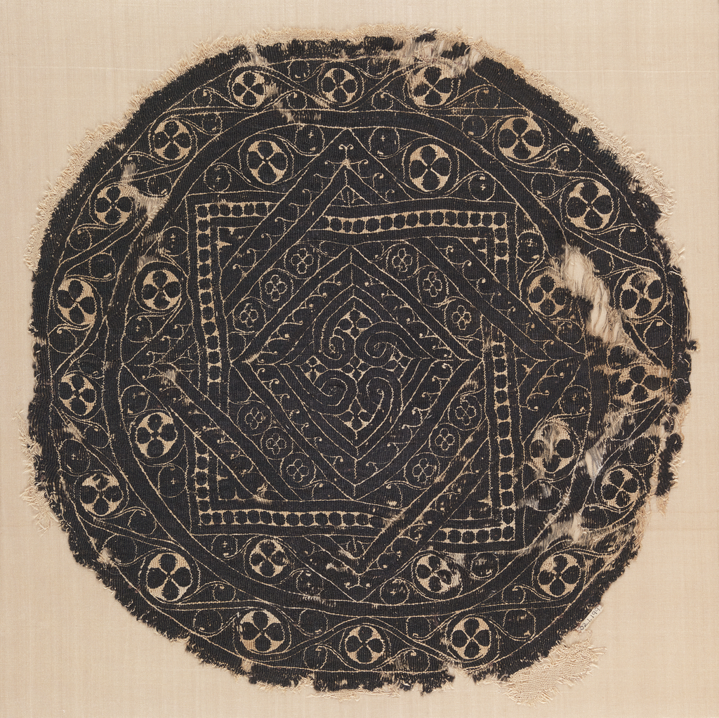Monochrome tapestry roundel with an eight-pointed star formed by two interlocking squares, containing a smaller square with half spirals. Border of four-lobed motifs in circles, connected by a curving linear element.
