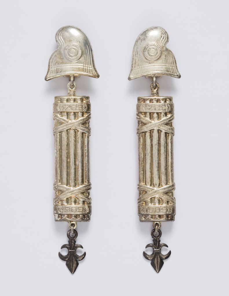 Pair of articulated drop earrings, each composed of three elements joined by loops. From the top: a phrygian cap, followed by a fasces stamped with the years 1789 and 1989 in bands at its top and bottom, followed by an upside-down fleur de lis. Each cap with a hinged clip on the back.