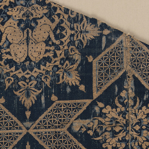 Fragment of woven silk with eight-pointed stars containing regardant leopards or cheetahs alternating with palmettes and leaf forms. The stars are formed from parallelograms with lattice-like fillings. The leopard or cheetah pairs are surrounded by inlaced bands and pointed foliage. In cream and gold on a dark blue ground.