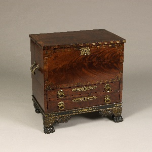 Upright, rectangular form; veneered surface with two drawers surmounted by a drop front panel with inlay of light wood bands around edges, stars at corners and gilt bronze escutcheon in form of trophy; drawers with gilt bronze circular pulls and palmette-form escutcheons; rectangular gilt bronze handles on left and right side; two paw feet with gilt foliate decoration in front; turned rear feet.