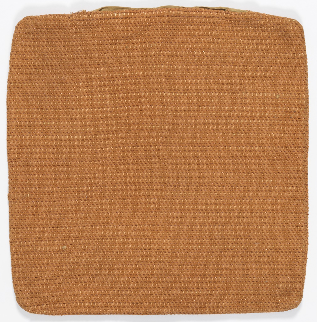 Pillow cover in a variety of different orange threads and Lurex yarns that has a textured appearance.