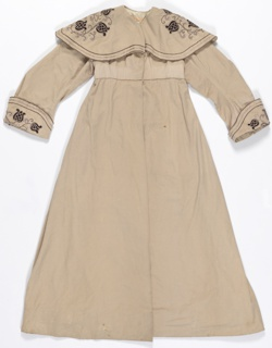 Light brown gown with matching belt has embroidered details on the collar and cuffs.