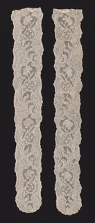 A pair of Mechlin-style lace cap streamers with gently scalloped edges and a scrolling ascending vine with flowers and Rococo forms filled with small diaper patterns.