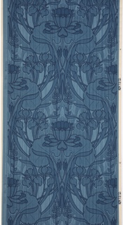 Floral design with large central flower positioned between two large leaves. Other types of flowers and foliage appear including iris blooms. Designed in the art nouveau style, the flowers and leaves gently curve and intertwine creating a dense pattern. Printed in shades of blue on a blue striped background.