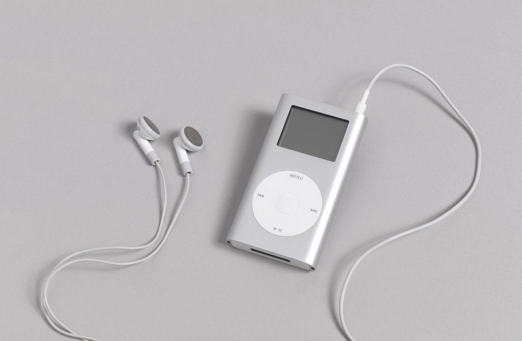"""Flat silver rectangular form with curved sides; white panels on top and bottom with switch and ports for cord and earphones; on front, clear rectangular digital readout screen above circular white control with the word """"Menu,"""" and arrow symbols for 'back,' 'forward,' 'pause.'"""