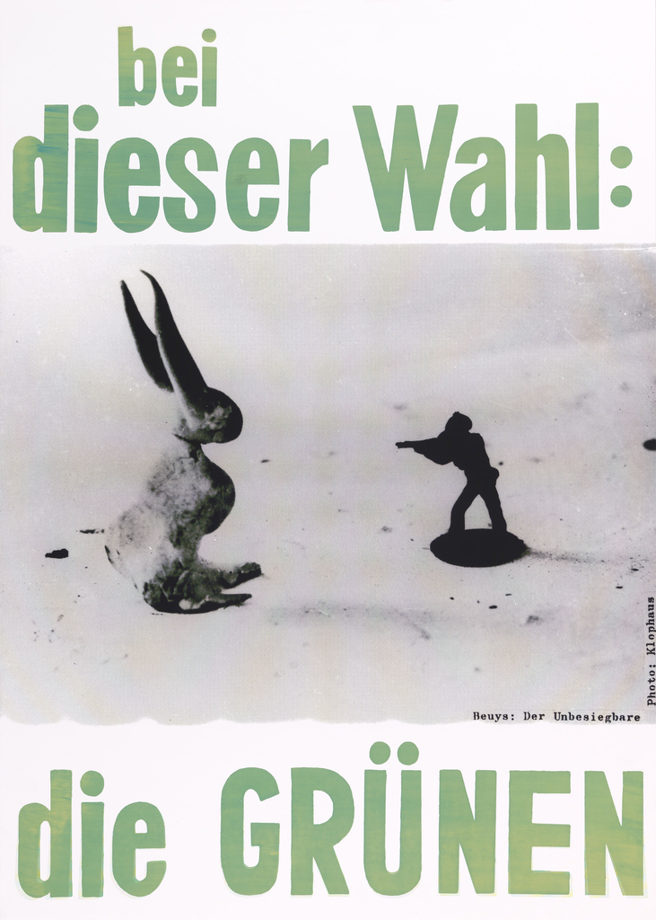 "Election Poster for the Green Party.  Text across top in green reads: ""bei dieser Wahl:"" with black and white photograph of toy soldier aiming gun at toy rabbit below. Underneath photo, at bottom of poster, text in green: ""die GRUNEN."""