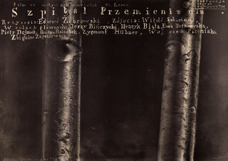 "Black poster with text across the top in white. Two black-and-white tree trunks with eyes.  Trunk at left has eye facing out towards viewer. Trunk at right has eye facing pole at left. Text across top in off-white reads: ""film na motywach powiesci St Lema/ Szpital Przemienienia/ Rezyseria: Edward Zebrowski, Zdjecia: Witold Sobocinski,/ W rolach glownych: Jerzy Binczycki, HenrykBista, Ewa Datkowska,/ Piotr Dejmek, Gustaw Holoubek, Zygmunt Hubner, Woj ciech Pszonuak/ Zbigniew Zapasiewicz."""