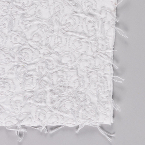 Sample of white jersey embroidered with white thread in a spiral pattern. Knotted on the surface and cut leaving threads that form a surface texture.