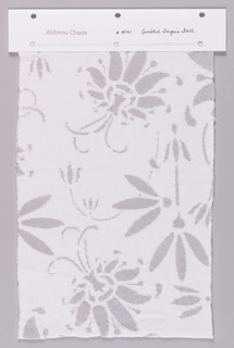 Sample of white jersey printed with a metallic silver floral pattern. Floral pattern is outlined in white thread.