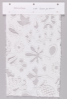 Sample of white jersey with a reverse appliqué of printed silver jersey in a pattern of leaves and flowers. White jersey cord is couched around the motifs.