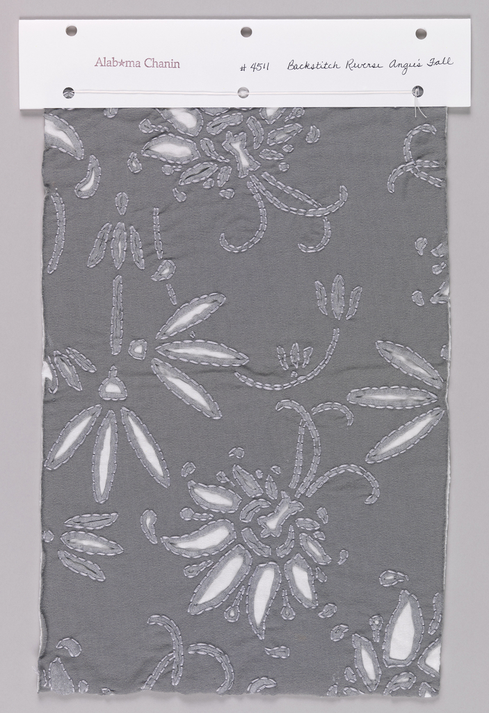 Sample of dark gray jersey with a reverse appliqué of white jersey in a floral pattern. Cut areas in dark gray jersey have light silver printed outlines. Backstitched details are in a light gray thread.
