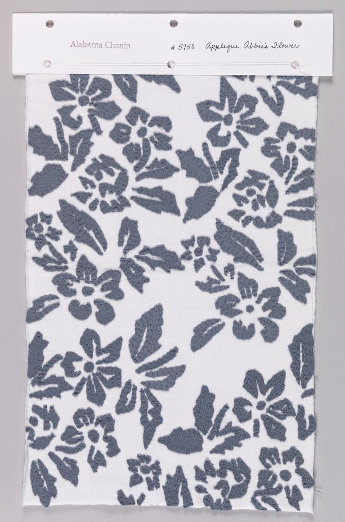 Sample of white jersey appliquéd in a floral design using dark blue jersey.