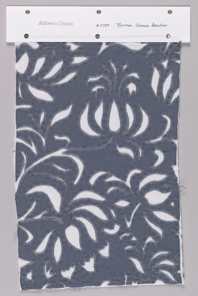 Sample of blue-gray jersey reverse appliqué with white jersey in a floral design.