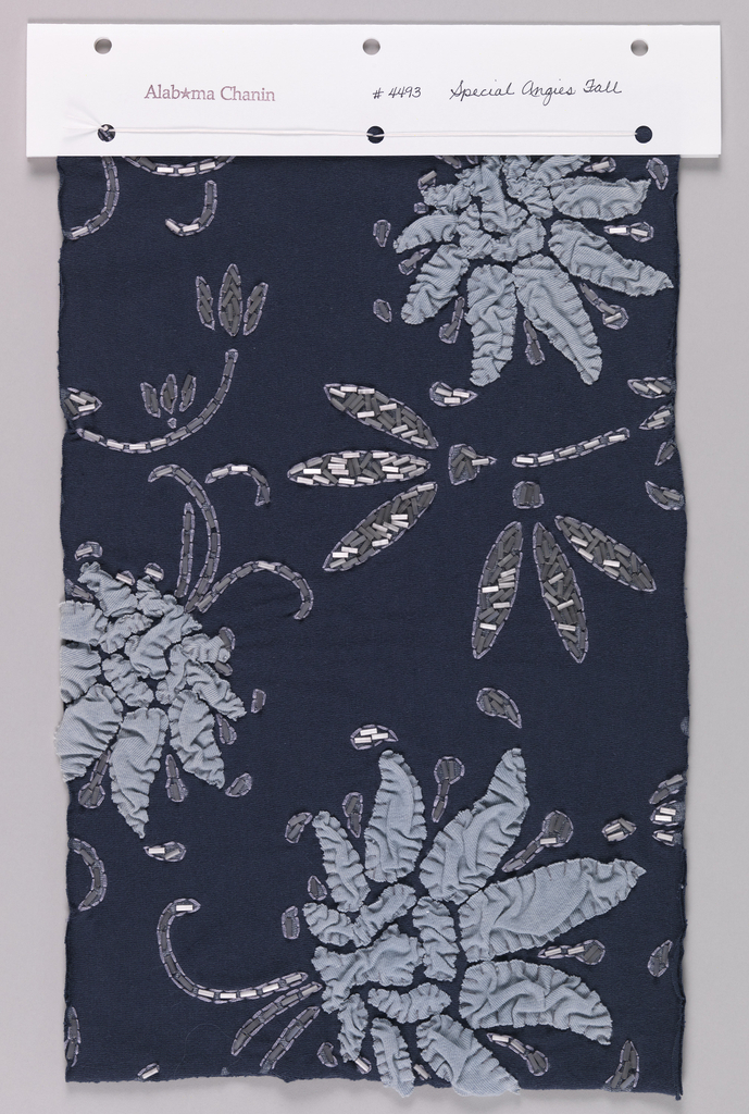 Sample of dark blue jersey appliquéd in a floral pattern with puckered light blue jersey and clear and white bugle beads. Bugle bead stems and leaves are outlined in light purple thread using a running stitch.