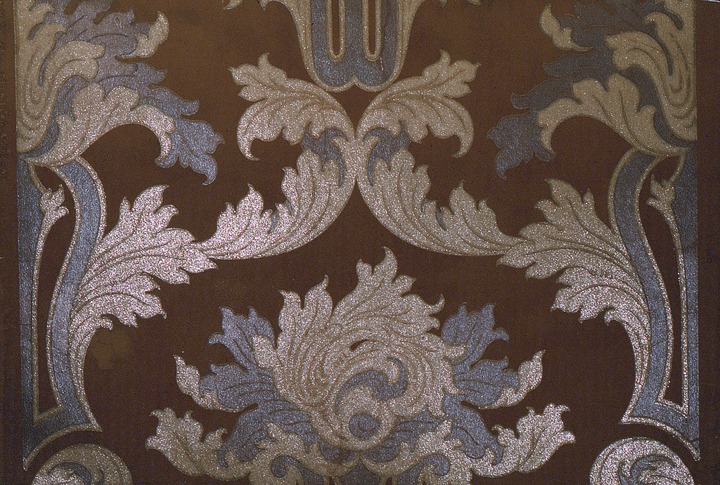 """Tobacco brown ground with conventional leaf scrolls in silver and gilt. Mica finish. Marked: """"Process patented July 19, 1892."""""""