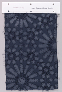 Sample of dark blue jersey appliquéd with metallic silver printed dark blue jersey in a pattern of large and small flower heads. Petals are attached to the foundation using a running stitch and are secured with knots. Knots are trimmed with excess thread remaining to form a surface texture.