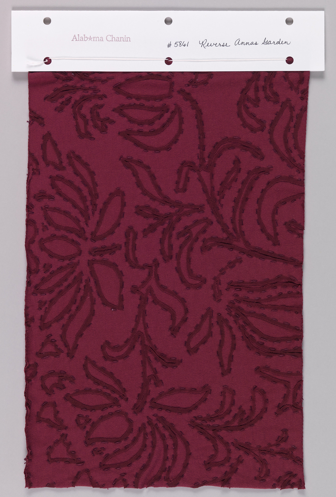 Sample of dark red jersey with a reverse appliqué of same jersey. Top layer has a cutout floral pattern and dark red outlines are printed around cut areas. Dark red stitching follows the printed outlines.