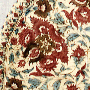 Round fragment of cream-colored cotton block printed in reds, violet, and green.  A floral pattern is arranged to fill a circle of flower heads. Center round medallion has a stylized flower head forming a rosette.