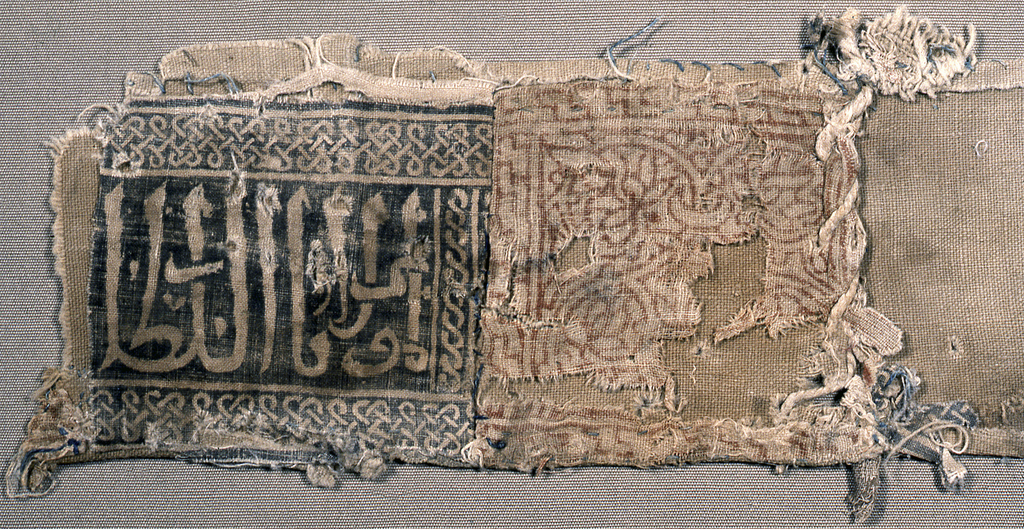 Two small horizontal panels joined by vertical seam. Left panel: Islamic inscription framed top and bottom by plait border, guilloche on right side - reserved on blackish ground. Right panel: rosette interlacing with lotus fillings and narrow interlacing boarder - reddish outlined on undyed ground.  Seemingly part of a cap-band with coarse undyed cotton lining and inner lining.  Translation of Islamic inscription: Glory to our Lord the Sultan.