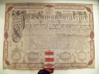 Horizontal rectangle. Certificate of membership in the guild of bookbinders issued by Simon Ibersperger to his son, Johannes, on 16 January 1750 upon his admission to the bookbinders guild at Klosterneuberg.  The calligraphy is very elaborate with a checkered red and black penwork border.  It is signed by four guild members in boxes prepared before signing.  A wooden seal of the guild dated 1651 hangs from two crimson ribbons attached to the vellum.