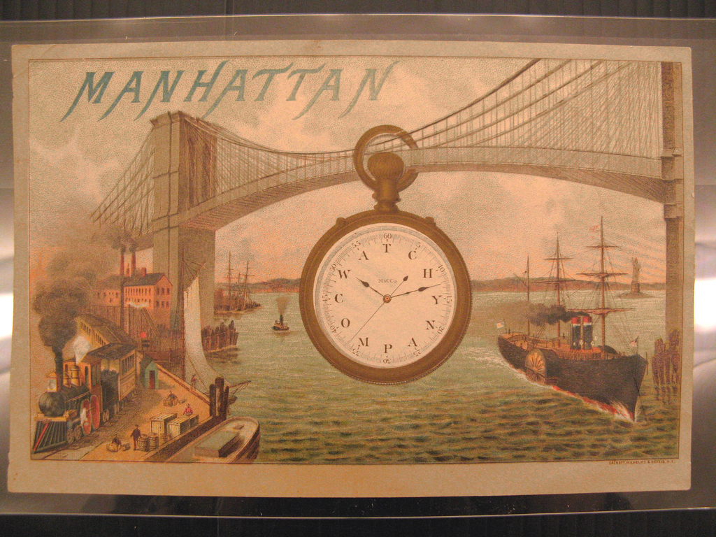 "Imagined vista of the harbor of Manhattan looking underneath the newly constructed Brooklyn Bridge.  A large pocketwatch floats in the center of the bridge trusses.  Inscribed on the face written in a concentric circle is: WATCH COMPANY.  The hands of the watch are set at 10:12.  ""MW & Co."" is written in small print at the center of the watch face.  At the upper left is written ""Manhattan"" in blue capital letters."