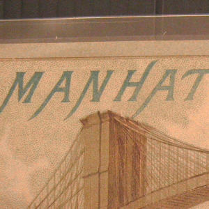 """Imagined vista of the harbor of Manhattan looking underneath the newly constructed Brooklyn Bridge.  A large pocketwatch floats in the center of the bridge trusses.  Inscribed on the face written in a concentric circle is: WATCH COMPANY.  The hands of the watch are set at 10:12.  """"MW & Co."""" is written in small print at the center of the watch face.  At the upper left is written """"Manhattan"""" in blue capital letters."""