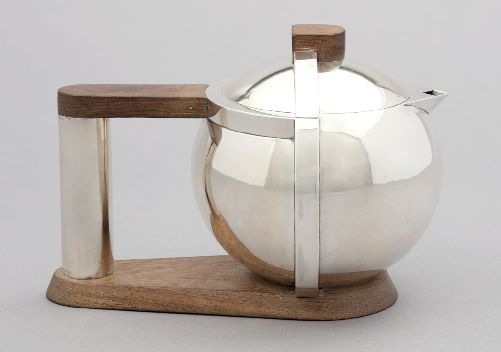 Globular body with flush-fitting domed cover.  Raised square band encircles body at right angle to handle, with shape continued on cover.  Triangular spout with lozenge-shaped opening.  Tubular handle attached to body with walnut strut at top, and to shaped plinth that continues as base of teapot body.  Shaped wooden finial.  Cover with fitted flange closure.