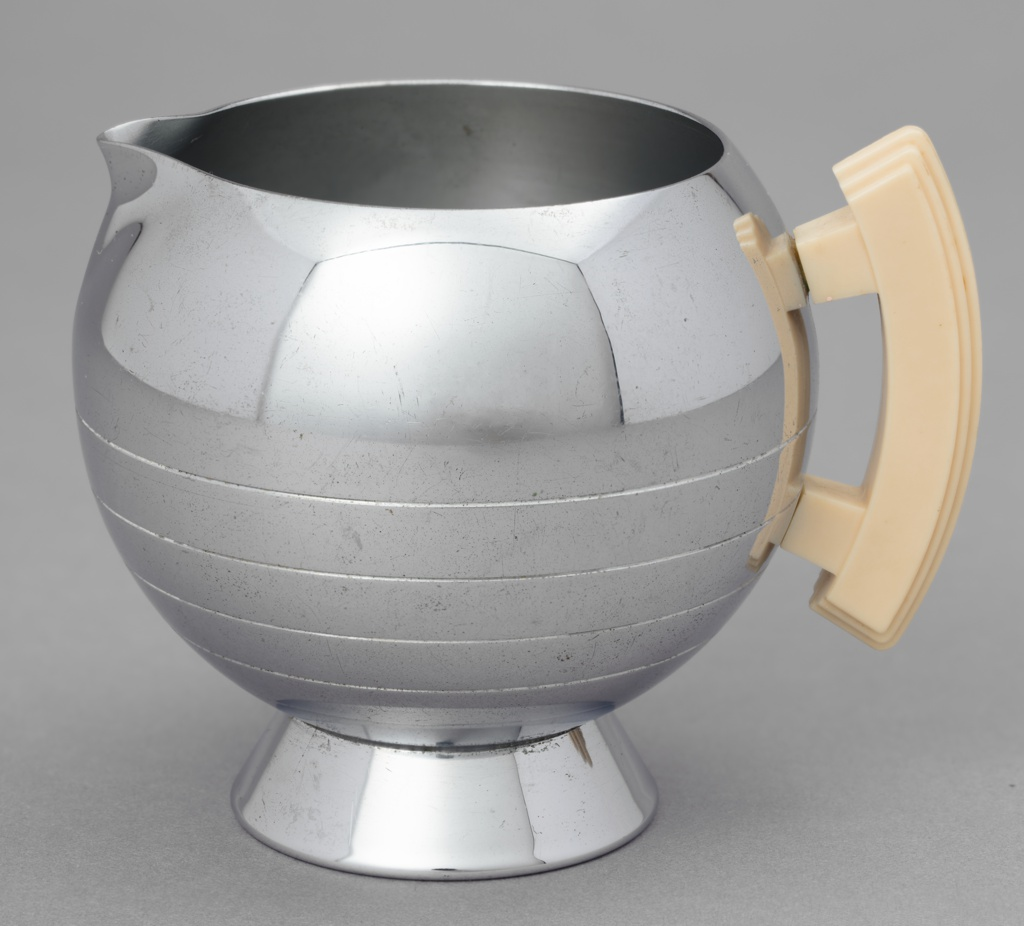 Spherical chrome creamer with an open top and small spout. Sugar bowl sits on a small chrome cylindrical base.