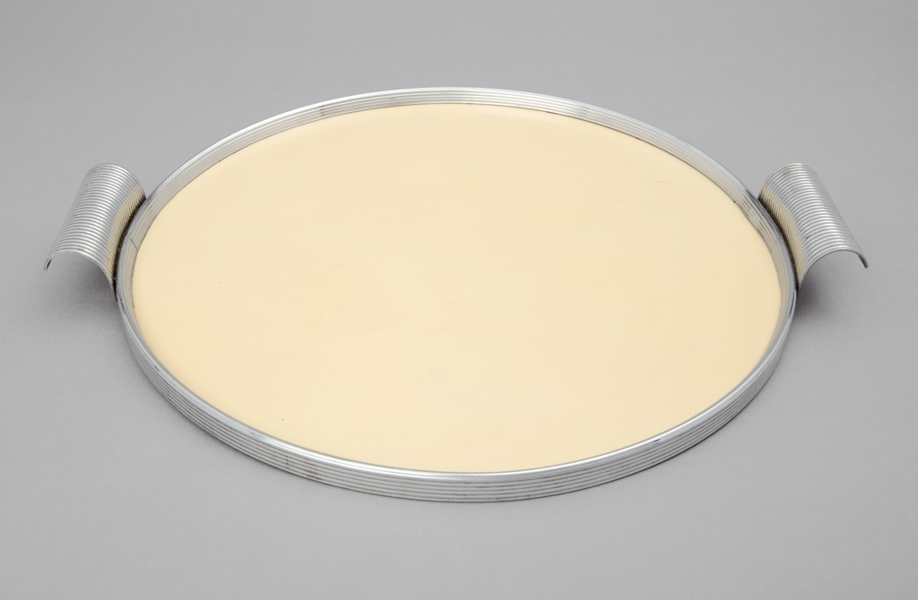 Circular tray composed of ridged chrome rim surrounding cream colored plastic base; two curved, ridged chrome handles on opposite sides.