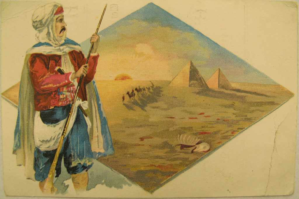 An arabian man standing with a long stick in front of a diamond shaped view of the desert and pyramids