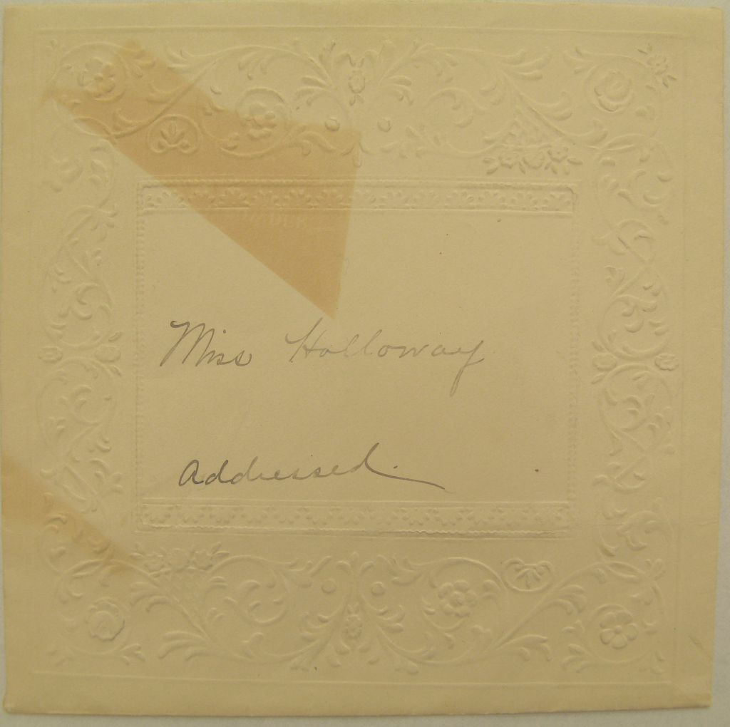 Square cream envelope with embossed borders.  There is a very wide border of floral branches that spring from the border's center with in a frame.  The center of the bordered region is large and has the following inscribed in graphite: Miss Holloway / addressed.  In the upper left quarter of the recto of the envelope is a large burn, with the shadow of another burn parallel to it.