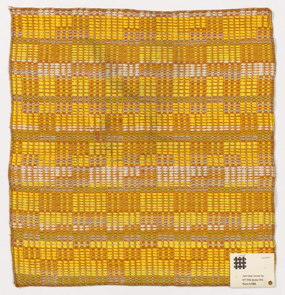 Sample of woven fabric has a variegated geometrical pattern made of thick and thin yarns in shades of yellow, orange, grey, and white.