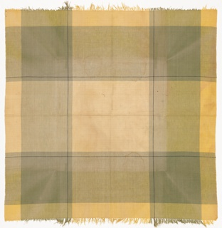 Square tablecloth has a wide plaid pattern in yellow, green, grey, and black.