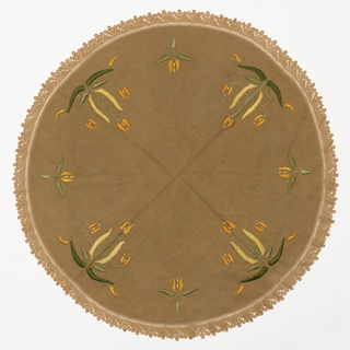Round Art & Crafts-style brown tablecloth has an embroidered floral design in green, orange and pale yellow. Crocheted border in the same color as the tablecloth. Likely purchased as an embroidery kit.