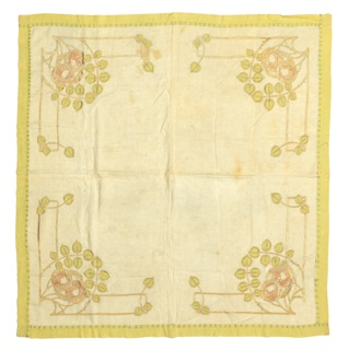 Square off-white tablecloth has in each corner two stylized pink roses with pale yellow-green spade-shaped leaves. Roses reminiscent of the Glasgow rose design.