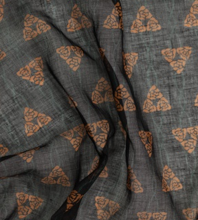 Length of sheer black fabric printed with a staggered repeat of three roses in dark orange connected vertically by twisted green cords.