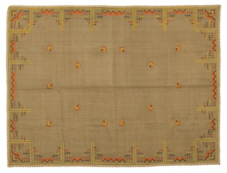 Rectangular brown tablecloth embroidered in a geometric and linear pattern of orange, brown and yellow.
